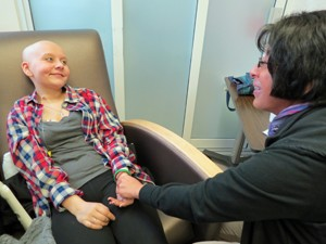 Two-for-one treatment: While Gailon receives a dose of chemotherapy, Artola stops by to treat her with acupressure.