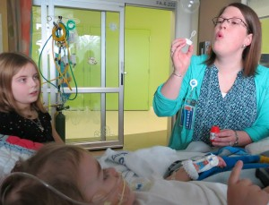 Child Life specialist Amie Lusk blows some distracting bubbles for Christian Lybbert on a difficult day while his sister, Izabella, watches.